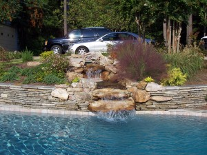 A pleasant cascade falls (or appears to fall) from the spa into the pool, adding a soothing and engaging kinetic element to the landscape.